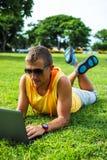 Homem novo que encontra-se na grama e que trabalha com portátil Fotografia de Stock Royalty Free