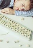 Homem novo que encontra-se na tabela com teclado Foto de Stock Royalty Free
