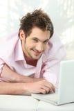 Homem novo que encontra-se no sofá Imagem de Stock
