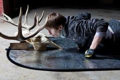 Homem novo que encontra-se para baixo olhando o crânio dos cervos em um porão escuro Fotografia de Stock