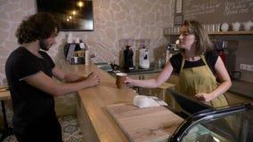 Homem novo que entra em uma cafetaria e que pede um café do latte do mocha para ir pagá-lo com um cartão sem contato - filme
