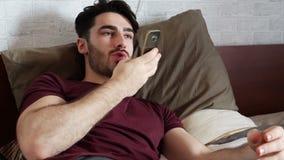 Homem novo que envia a mensagem da voz no telefone na cama vídeos de arquivo