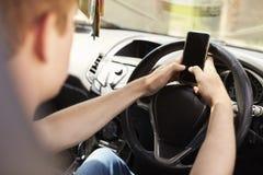 Homem novo que envia a mensagem de texto enquanto conduzindo Foto de Stock