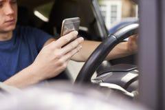 Homem novo que envia a mensagem de texto enquanto conduzindo Fotografia de Stock