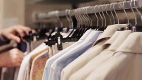 Homem novo que escolhe a roupa na loja de roupa filme