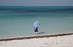 Homem novo que esconde do sol sob uma toalha Imagens de Stock