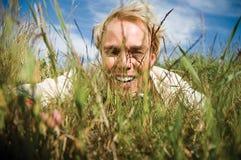 Homem novo que esconde na grama Fotografia de Stock