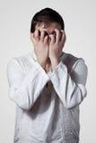 Homem novo que esconde sua face com mãos Fotografia de Stock