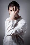 Homem novo que esconde sua face com mão Fotografia de Stock Royalty Free