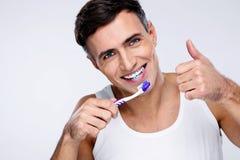 Homem novo que escova seus dentes Imagem de Stock