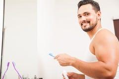 Homem novo que escova seus dentes em um banheiro fotografia de stock