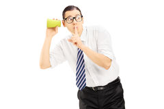Homem novo que escuta através da parede com um copo e que gesticula o si Imagem de Stock