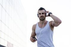 Homem novo que escuta a música ao tomar uma ruptura do exercício imagem de stock