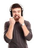 Homem novo que escuta a música e que morde um fio Fotos de Stock Royalty Free