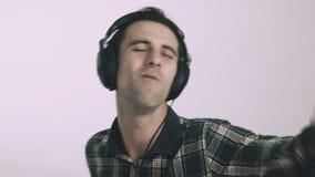 Homem novo que escuta a música em auscultadores filme