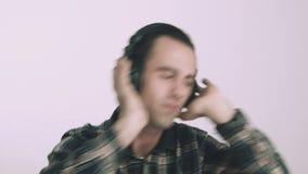 Homem novo que escuta a música em auscultadores video estoque