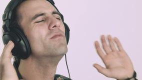 Homem novo que escuta a música em auscultadores vídeos de arquivo