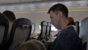 Homem novo que escuta a música em fones de ouvido através do telefone celular Um homem de negócios durante o voo está olhando um  vídeos de arquivo