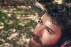 Homem novo que escuta a música na floresta Foto de Stock Royalty Free