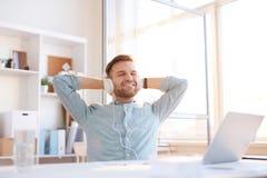 Homem novo que escuta a música no local de trabalho imagens de stock royalty free