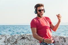 Homem novo que escuta a música nos fones de ouvido que jogam a guitarra imaginária Imagens de Stock Royalty Free