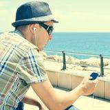 Homem novo que escuta a música ou que fala com fones de ouvido em um sma Fotografia de Stock Royalty Free