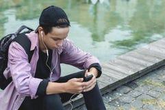 Homem novo que escuta a música que senta-se no passeio Foto de Stock