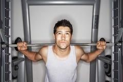 Homem novo que esforça-se para levantar peso foto de stock