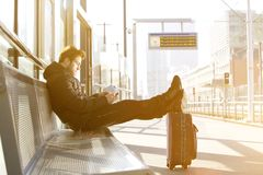 Homem novo que espera na plataforma do estação de caminhos-de-ferro com telefone celular imagem de stock