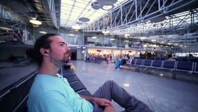 homem novo que espera o seu voo na sala de estar do aeroporto vídeos de arquivo