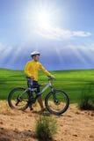 Homem novo que está ao lado da bicicleta do moutain, mtb no monte com shi do sol Fotografia de Stock
