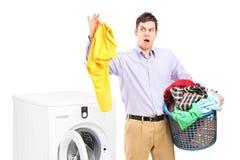 Homem novo que está ao lado de uma máquina de lavar   imagens de stock