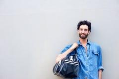 Homem novo que está com o saco do curso sobre o ombro imagens de stock royalty free
