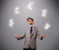 Homem novo que está e que manipula com ícones da moeda Imagem de Stock