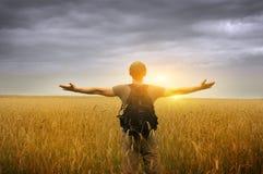 Homem novo que está em um campo de trigo Imagens de Stock