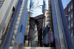 Homem novo que está na escada rolante com saco imagens de stock