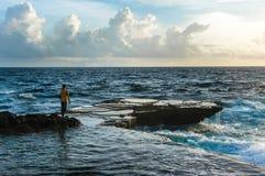 Homem novo que está na frente das ondas raging do mar e de quebra Fotografia de Stock
