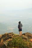 Homem novo que está na parte superior de uma montanha e que aprecia a opinião do vale Foto de Stock