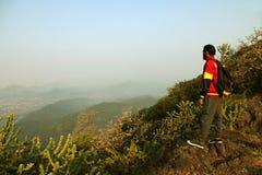 Homem novo que está na parte superior de uma montanha e que aprecia a opinião do vale Fotografia de Stock