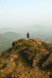 Homem novo que está na parte superior de uma montanha e que aprecia a opinião do vale Fotos de Stock Royalty Free
