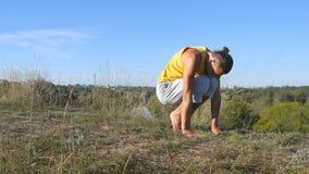Homem novo que está na pose da ioga na natureza Movimentos e posições praticando da ioga do indivíduo fora Atleta que faz a força vídeos de arquivo