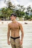 Homem novo que está na praia pelo oceano imagem de stock royalty free