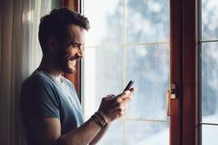 Homem novo que está pela janela usando um smartphone Fotos de Stock Royalty Free