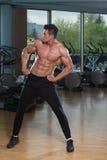 Homem novo que estica antes de exercitar no fitness center Imagem de Stock Royalty Free