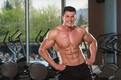 Homem novo que estica antes de exercitar no fitness center imagem de stock
