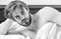 Homem novo que estica ao acordar na manh? Imagem que mostra o homem novo que estica na cama Acorde a manh? fotografia de stock royalty free