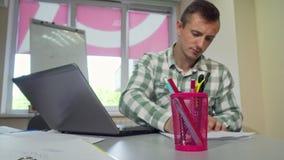 Homem novo que estuda na biblioteca de faculdade, lápis de agarramento do suporte de copo na parte dianteira video estoque
