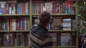 Homem novo que estuda um livro e que põe o sobre a prateleira em uma livraria vídeos de arquivo