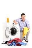 Homem novo que esvazia uma máquina de lavar Imagem de Stock Royalty Free