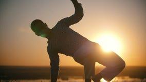 Homem novo que executa elementos do capoeira no monte no por do sol bonito filme